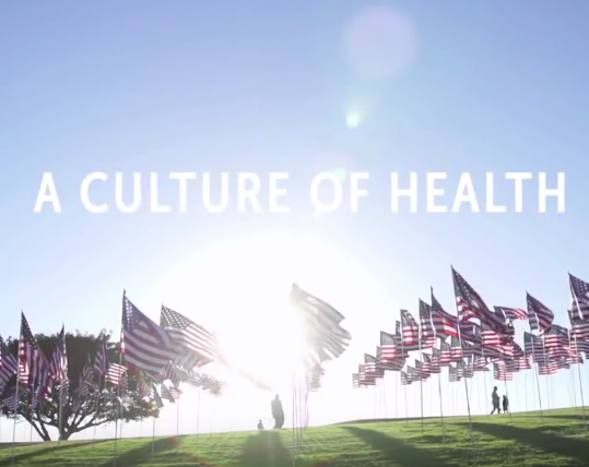 The words a culture of health displayed with an image of a grassy field and American flags